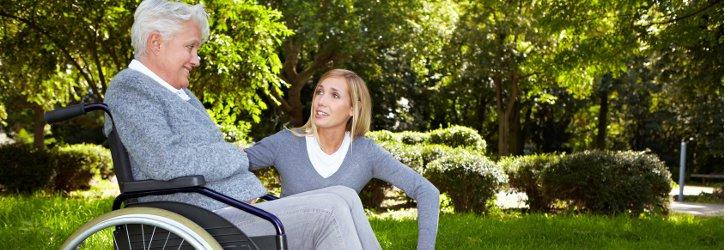 Frau redet mit Rollstuhlfahrerin im Park  Foto Fotolia